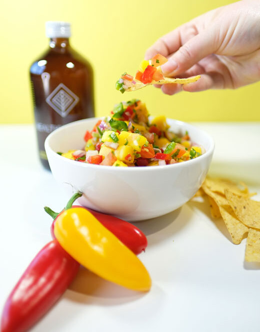 persons hand scooping mango salsa onto a tortilla chip