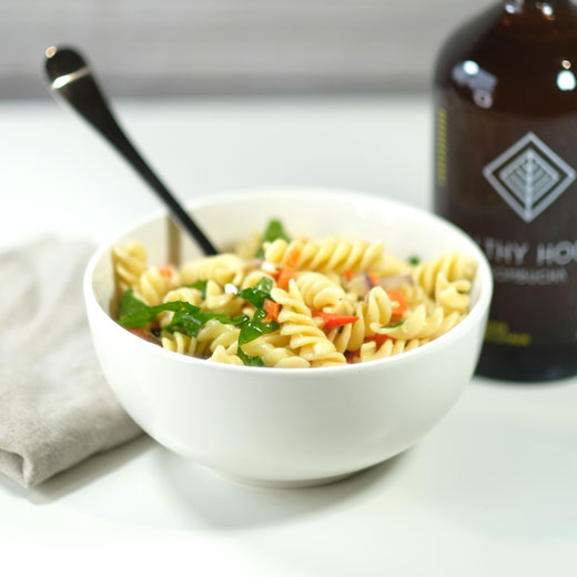 pasta salad next to a bottle of kombucha