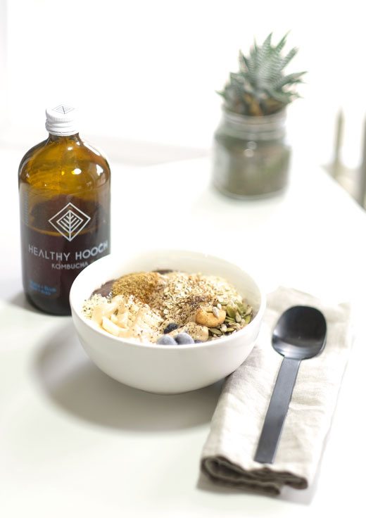 smoothie bowl next to toppings and a bottle of kombucha