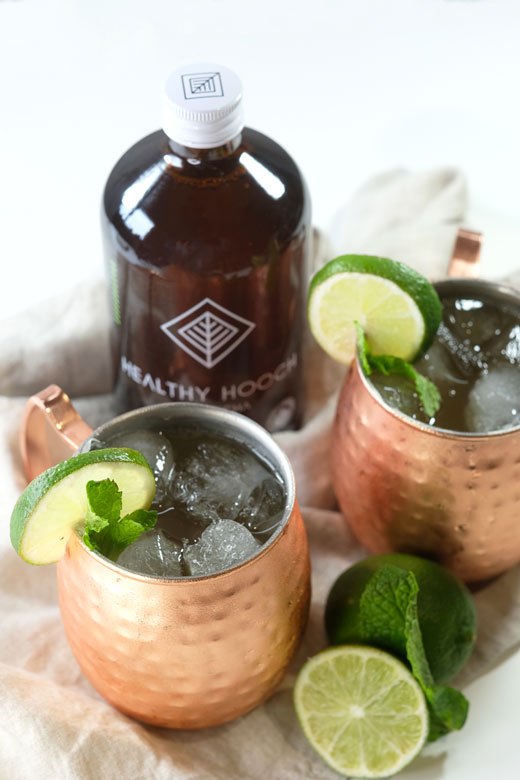 two copper moscow mule glasses with a bottle of healthy hooch kombucha