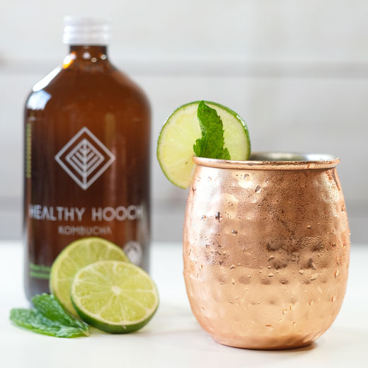 moscow mule next to a bottle of healthy hooch with some limes
