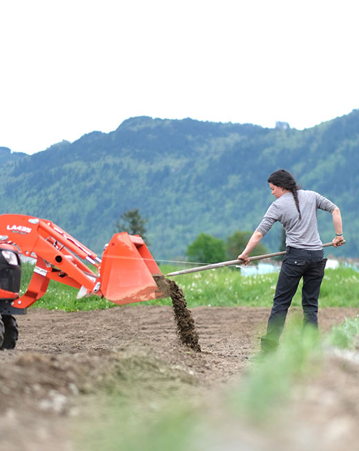 woman unloading soil from a tractor