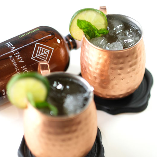 moscow mules next to a bottle of kombucha