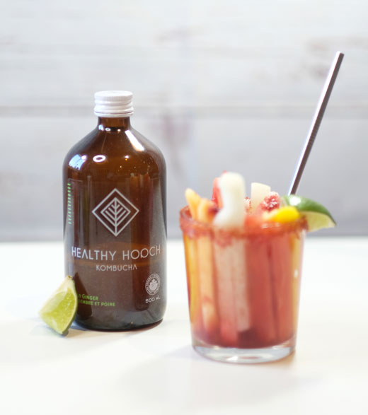 Mexican fruit cup next to a bottle of kombucha