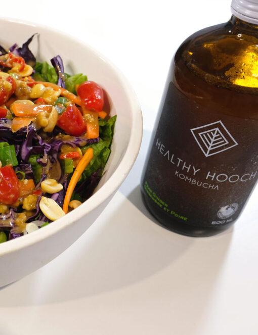 colourful chopped salad next to a bottle of kombucha
