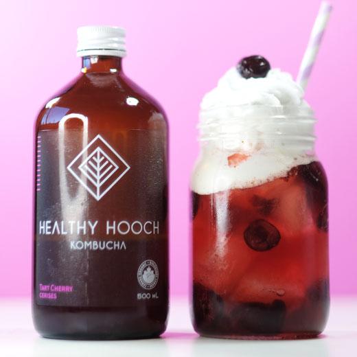 cherry float next to a bottle of kombucha