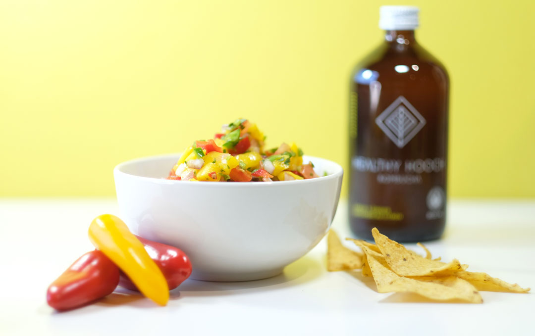 mango salsa next to peppers, tortilla chips and a bottle of kombucha