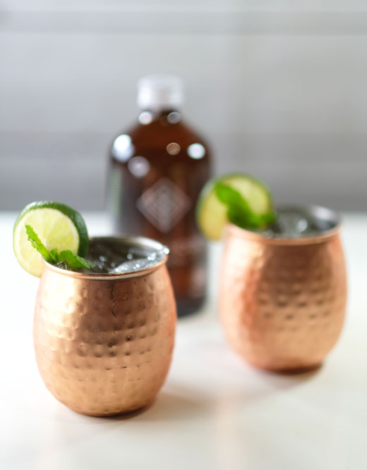 moscow mules with a bottle of kombucha in the background