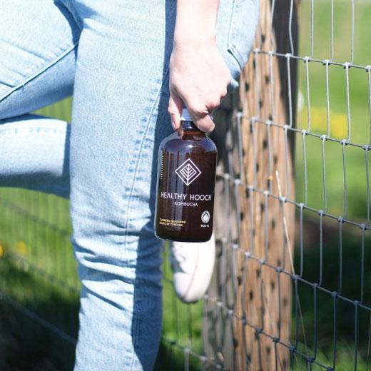 girl holding a bottle of turmeric sunshine kombucha