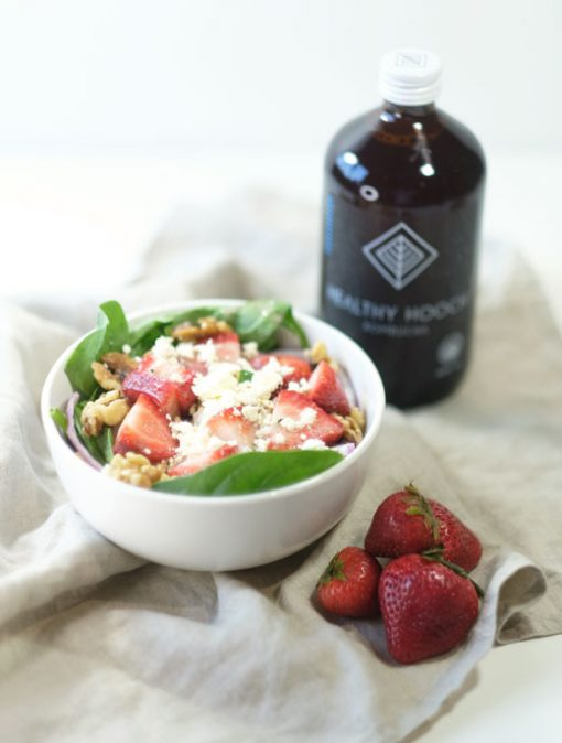 summer salad next to some strawberries and a bottle of healthy hooch kombucha