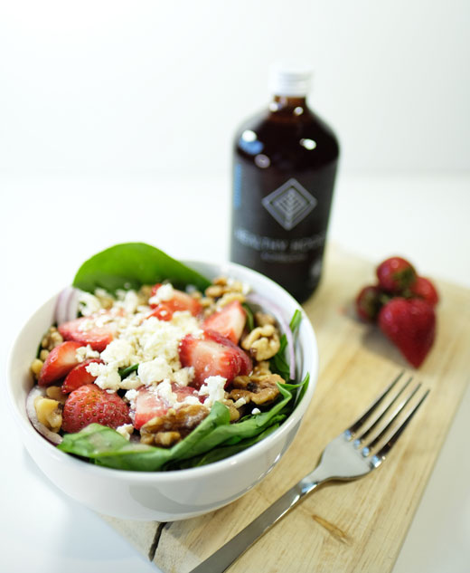 summer salad next to a bottle of healthy hooch kombucha and some berries