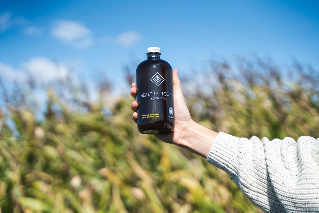 bottle of healthy hooch in front of a field