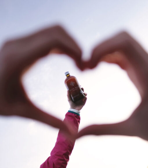 woman's hands making the shape of a heart with a bottle in the background