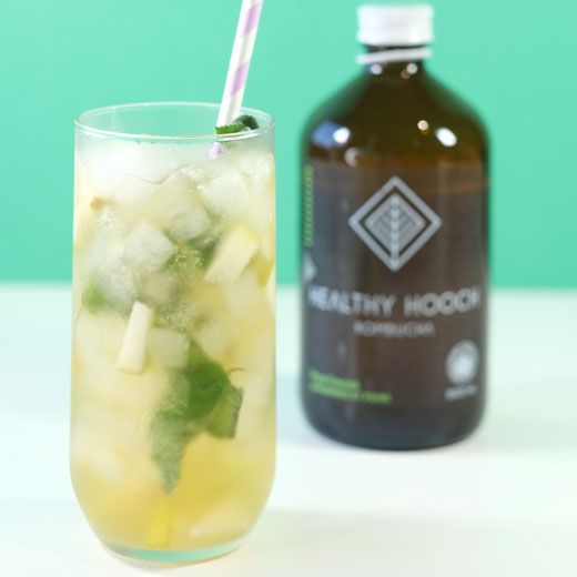 pear ginger mojito mocktail next to a bottle of healthy hooch kombucha