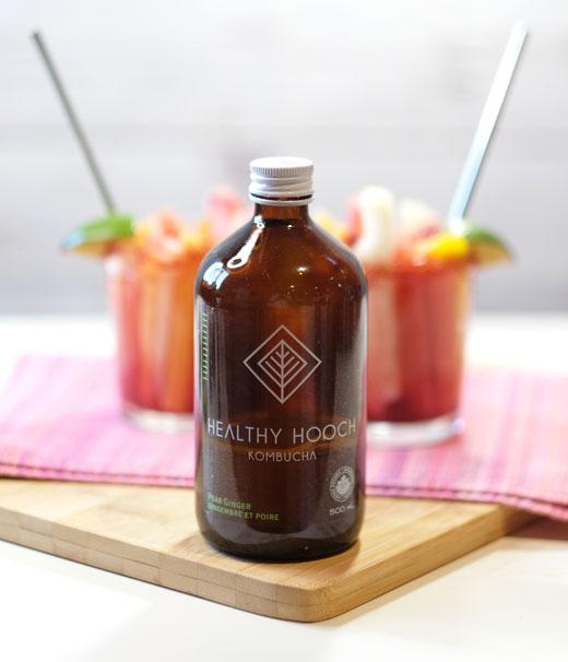 bottle of healthy hooch kombucha in front of two Mexican fruit cups