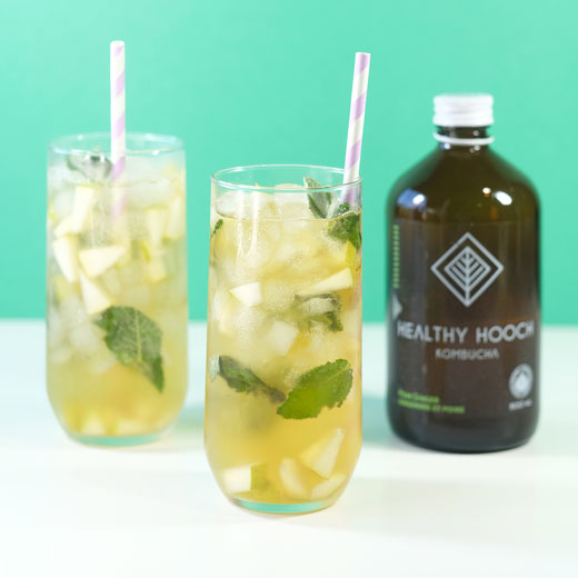 pear ginger mojito mocktails next to a bottle of healthy hooch kombucha