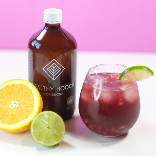 tart cherry pomegranate mocktail next to a bottle of healthy hooch kombucha and some fruit