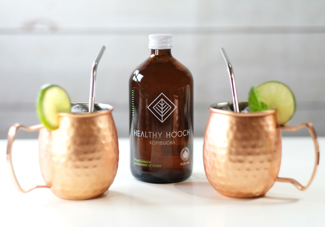 two copper moscow mule glasses with a bottle of healthy hooch