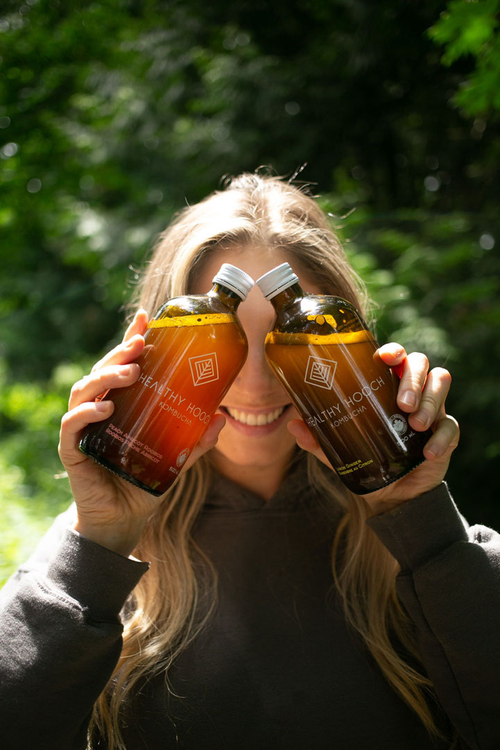 Girl holding two bottles of healthy hooch kombucha in front of her eyes