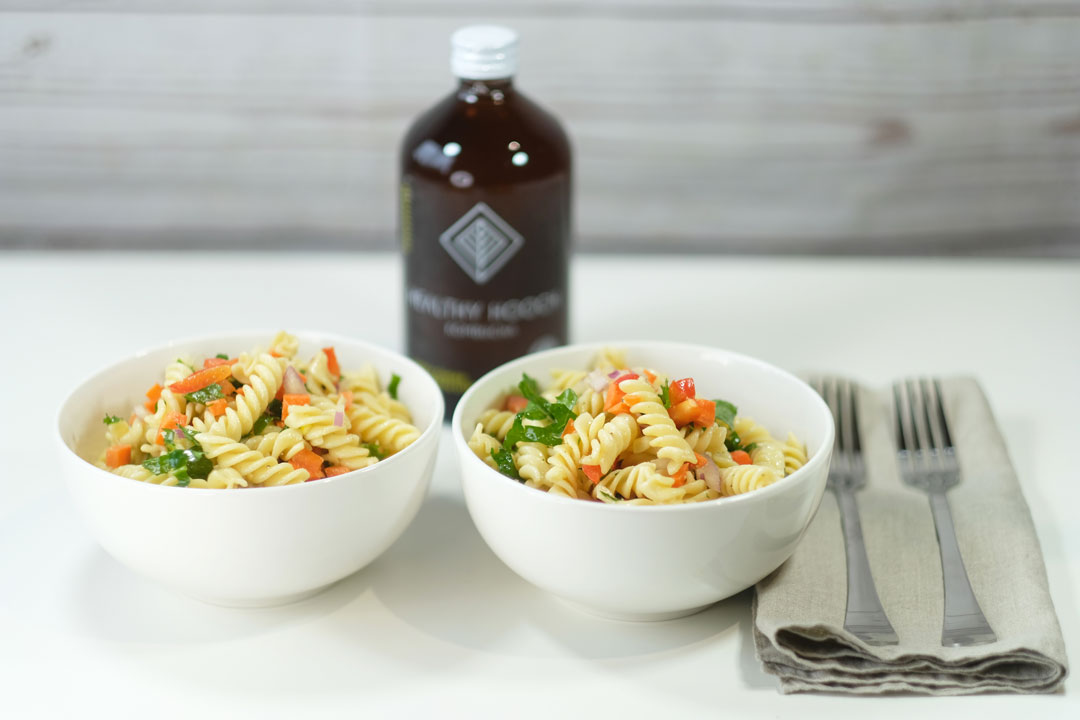 two bowls of pasta salad next to a bottle of kombucha