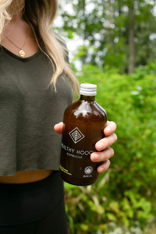 girl holding a bottle of healthy hooch kombucha