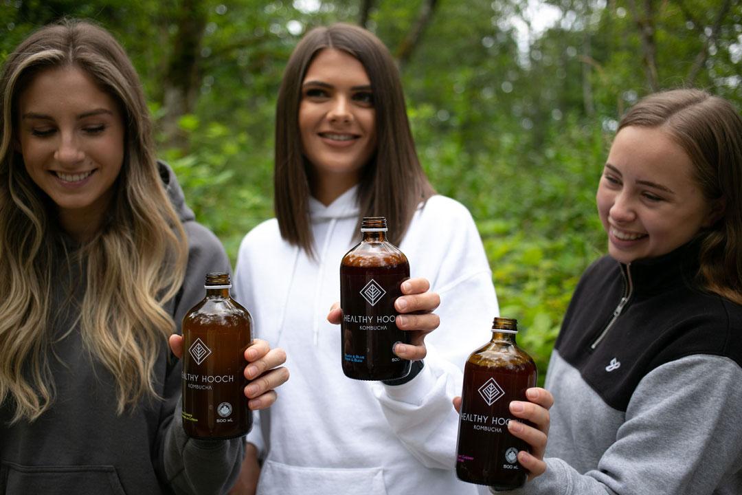 three girls standing in a line enjoying bottles of healthy hooch kombucha