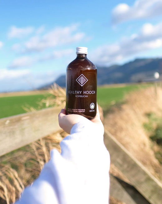 bottle of certified organic healthy hooch with the farm in the background