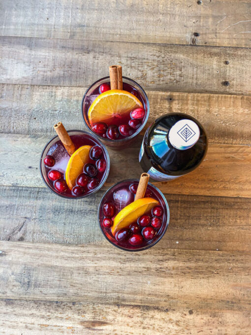 3 glasses of mulled wine kombucha cocktail on a wood table next to a bottle of the seasonal kombucha